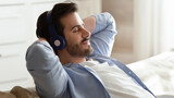 Close up of calm young Caucasian man in headphones relax on sofa at home listen to music take nap. Millennial male in earphones rest on couch breathe fresh air, enjoy good quality sound on device.