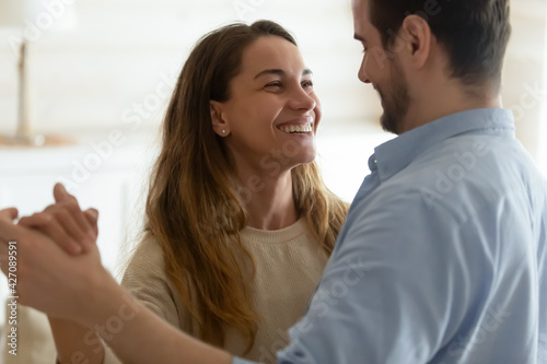 Fototapeta Happy millennial multiethnic man and woman dance waltz together at home, show love and affection in relationship