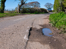 A Blue Farm Tractor Approaches Surface Damage To Tarmac On A Rural Road Is Marked For Repair With White Spray Paint. Taken On Wirral In The UK On A Sunny Day In Spring.