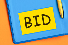 Bid The Word Is Written In Black Letters On The Yellow Paper For Notes