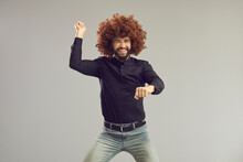 Let's Have A Party. Happy Young Man With Funny Crazy Hair Having Fun In Studio. Carefree Goofy Guy Wearing Curly Wig Smiling And Dancing Gangnam Style Isolated On Gray Background