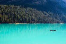 Solo Canoe In Empty Turqouise Blue Glacial Lake Surrounded By Natural Wilderness Forest And Mountain
