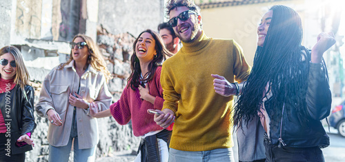 Group of young Friends gathering in the street listening music from smartphone and dancing together. Multiracial millennials having fun outdoors joking together. focus on the African descent woman.