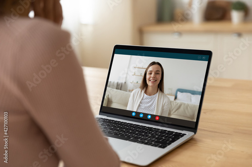 Two young women good friends sisters colleagues have fun chat by video call enjoy pleasant internet conversation via e conference app. Rear view of female teacher talk to student using laptop webcam