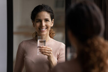 Easy Body Care. Beautiful Latina Lady Stand By Mirror At Home Hold Glass Of Water Smile Look At Reflection. Pretty Young Woman Enjoy Fresh Skin Healthy Look Effect Of Drinking Enough Aqua Every Day