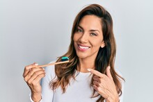 Young Latin Woman Holding Toothbrush With Toothpaste Smiling Happy Pointing With Hand And Finger