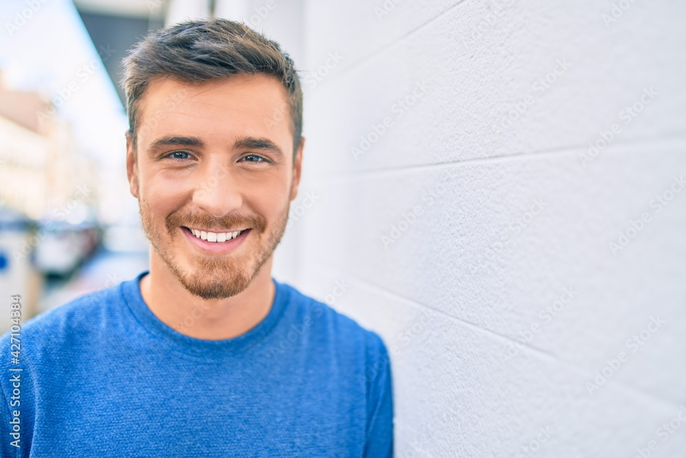 Fototapeta Young caucasian man smiling happy leaning on the wall at the city.