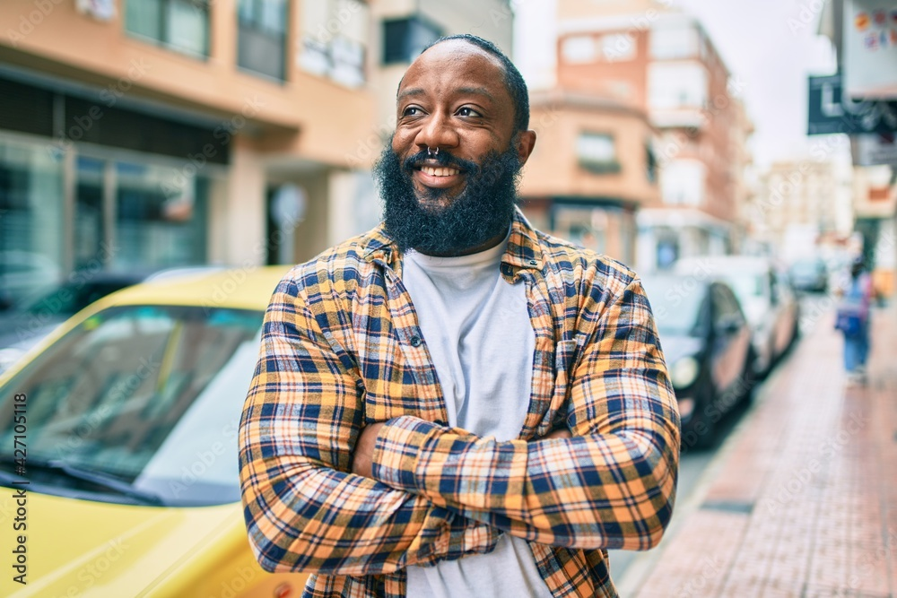 Fototapeta Handsome modern african american man with beard smiling positive standing at the street