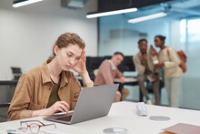 Portrait Of Stressed Young Woman Using Laptop In Office Or Coworking Space With Group Of People In Background, Copy Space