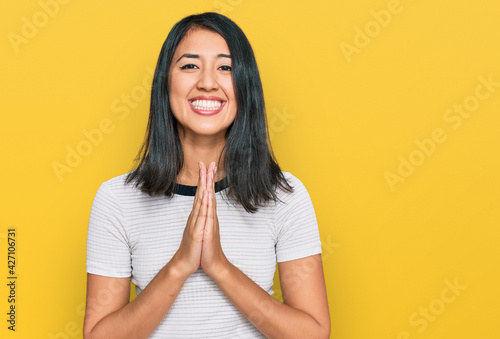 Leinwand Poster Beautiful asian young woman wearing casual white t shirt praying with hands together asking for forgiveness smiling confident
