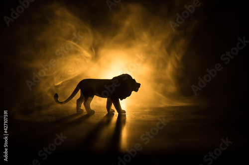 Fotografia A silhouette of lion miniature standing on wooden table