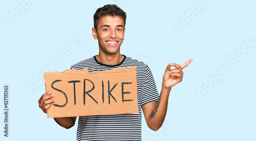Photo Young handsome african american man holding strike banner cardboard smiling happ