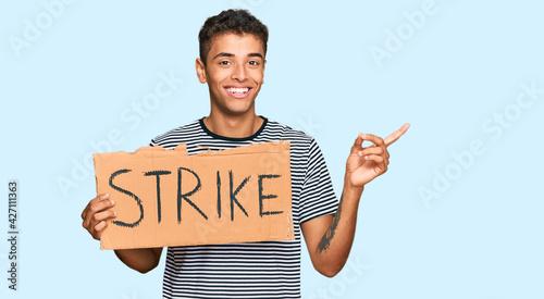 Fotografia, Obraz Young handsome african american man holding strike banner cardboard smiling happ