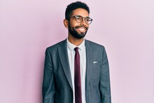 Handsome Hispanic Business Man With Beard Wearing Business Suit And Tie Looking Away To Side With Smile On Face, Natural Expression. Laughing Confident.