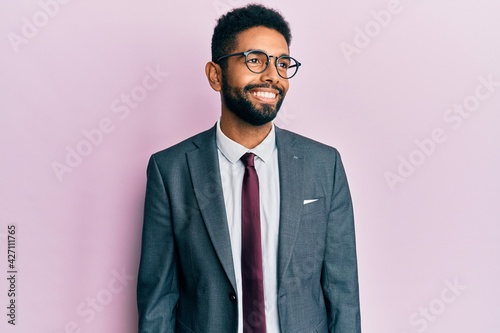 Papel de parede Handsome hispanic business man with beard wearing business suit and tie looking away to side with smile on face, natural expression