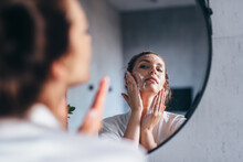 Woman Washes Her Face In Front Of The Mirror, Applying Foam To Her Cheeks