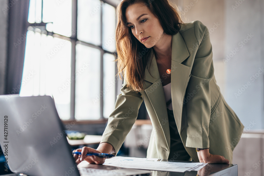 Fototapeta Woman stands leaning on her desk and uses her laptop