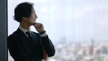 窓の外を眺めるビジネスマン