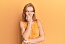 Young Caucasian Woman Wearing Casual Style With Sleeveless Shirt Looking Stressed And Nervous With Hands On Mouth Biting Nails. Anxiety Problem.