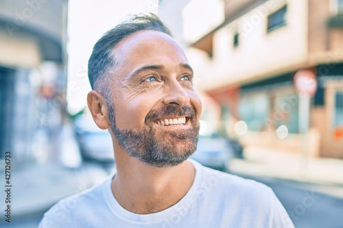Middle age handsome man smiling happy looking to the side at the city.