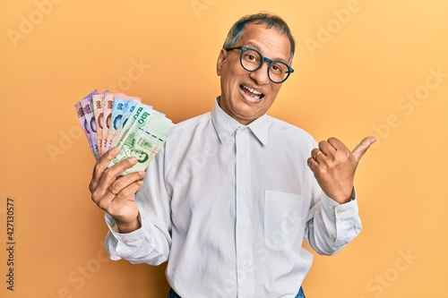 Obraz na plátne Middle age indian man holding thai baht banknotes pointing thumb up to the side