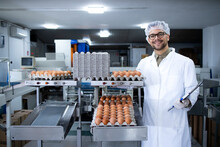 Portrait Of Food Factory Technologist With Hairnet And Hygienic Gloves Standing By Industrial Transporting And Packing Eggs Machine In Food Processing Plant.