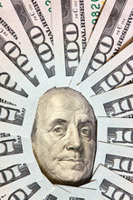 A Lot Of Folded One Hundred 100 USD Bills Layed Like Vintage Sun Face Beams Around Benjamin Franklin Portrait From 100 Dollar US Bill American Currency. Concept Of Wealth And Affluence Vertical.