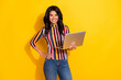 Photo of charming dark skin lady put hand on waist hold laptop toothy smile isolated on yellow color background
