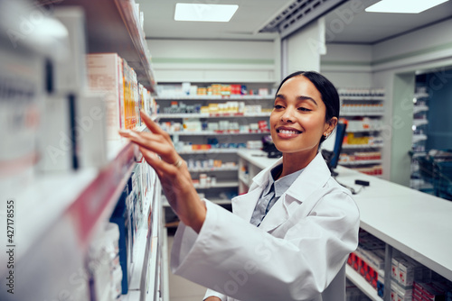 canvas print motiv - StratfordProductions : Smiling young female pharmacist wearing labcoat standing behind counter looking for medicine in shelf