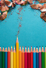 Top View. Colored Pencils Side By Side With The Yellow Pencil Pointing To The Top, A Path Of Colored Shavings Leads To The Remains Of The Pencil Tips.