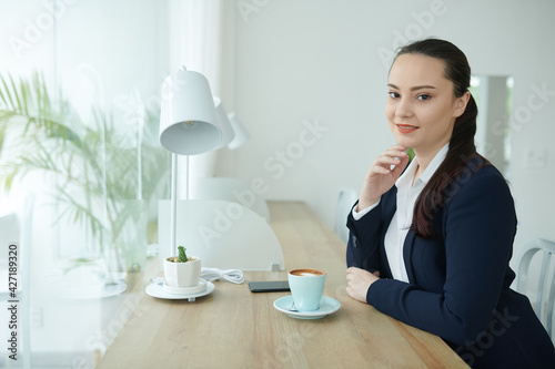 Fotografia Portrait of beautiful smiling young businesswoman sitting at table with cup of c