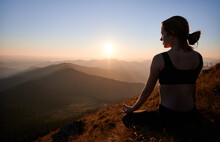 Woman Practicing Yoga In Lotus Pose In The Mountains In The Evening. Meditating Female Is Relaxing On Grass And Watching Sunset. Concept Of Harmony With Nature.