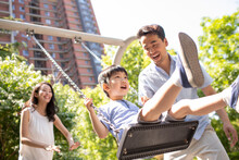 Happy Young Parents Pushing Son On Swing