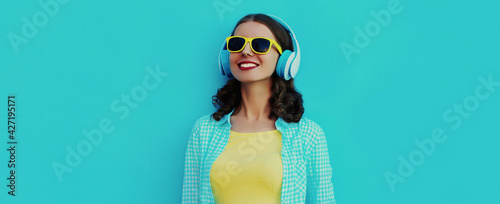 Fototapeta Portrait close up of smiling young woman with headphones listening to music on a blue background obraz