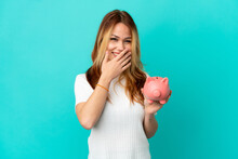 Teenager Blonde Girl Holding A Piggybank Over Isolated Blue Background Happy And Smiling Covering Mouth With Hand