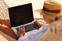 Young Woman Female Freelancer Using Laptop While Lying In Hammock On The Tropical Beach At Sunset
