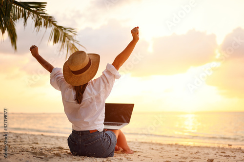 Tela Rear view of young female freelancer in straw hat celebrating success
