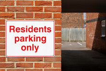 A Sign On The Wall Of An Apartment Block Stating Residents Parking Only
