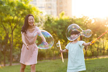 Happy Young Mother And Daughter Blowing Bubbles On Grass