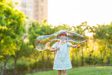 Happy Little Girl Blowing Bubbles On Grass