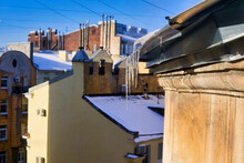 View Of Snow-covered Roofs With Spring Icicles Against Blue Sky