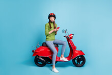 Full Length Photo Portrait Of Shocked Woman Holding Phone In Two Hands Sitting On Red Scooter Isolated On Pastel Blue Colored Background