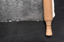 Wooden Rolling Pin And Flour On Black Background Top View.