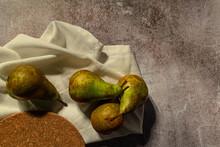 Bodegón De Peras Con Su Mantel Y Un Fondo Rústico, Ricas Frutas Fotografiadas