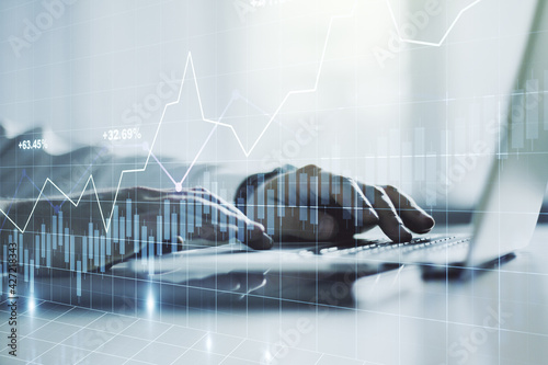 Multi exposure of abstract creative financial graph with hand typing on laptop on background, forex and investment concept
