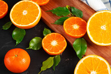Cut Oranges On Wooden Board On Table