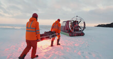 Rescue Service Team Loading Victim On Stretcher In Air-boat Patrolling Coast In Winter