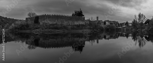 panoramic view of a wall and church tower in black and white reflected in a lake Fototapet