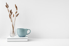 Mug And Transparent Vase With Flowers On A White Background. Eco-friendly Materials In The Decor Of The Room, Minimalism. Copy Space, Mock Up