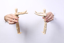 Female Hands Holding Wooden Puppets Through Torn Hole White Paper. Puppeteer. Minimalism